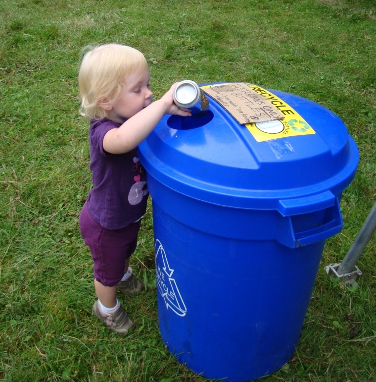 child placing can in blue recycling bin
