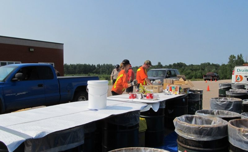OVWRC staff receiving hazardous waste at a dropoff event barrels laid our for sorting materials into
