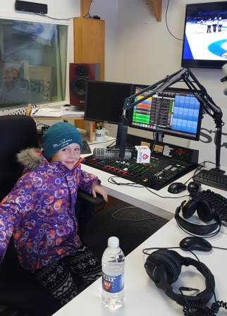 young girl sitting at microphone in local radio station