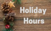wood background with Christmas greenery with Text Holiday Hours