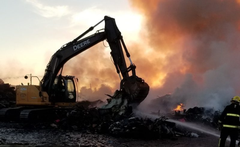 excavator moving materials and fire fighter spraying water